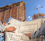 Engineers with building plans at high-rise construction site, close-up